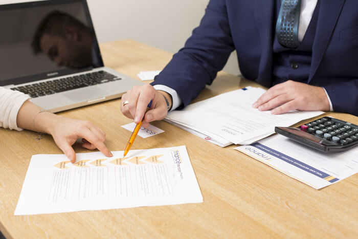 Two people at desk with paperwork Remortgage J Finance